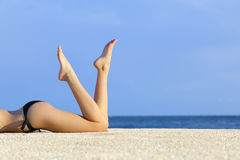 Piernas modelo lisas hermosas que descansan sobre la arena de la playa