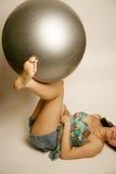 Piernas que aprietan la bola del exerise Imagen de archivo libre de regalías