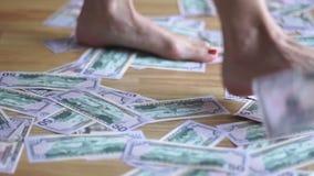 Piernas que caminan de la muchacha en el dinero almacen de metraje de vídeo