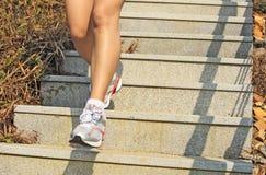 Piernas que corren para arriba en las escaleras de la montaña Imagen de archivo