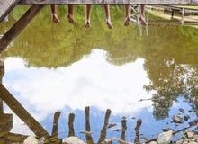Piernas que cuelgan abajo del embarcadero de madera sobre el agua Imagen de archivo