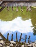 Piernas que cuelgan abajo del embarcadero sobre el agua Foto de archivo