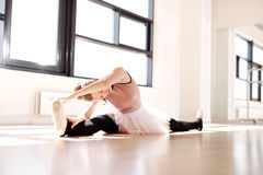 Piernas que parten de la bailarina mientras que alcanza sus dedos del pie Imagen de archivo libre de regalías
