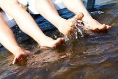 Piernas que salpican el agua Imagenes de archivo