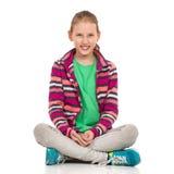 Piernas que se sientan sonrientes de la muchacha adolescente rubia cruzadas foto de archivo