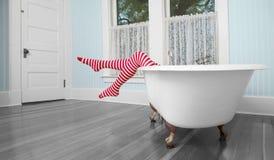 Piernas rayadas sobre la tina de baño en cuarto de baño del vintage imágenes de archivo libres de regalías