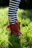 Piernas rayadas y botas rojas en hierba. Foto de archivo