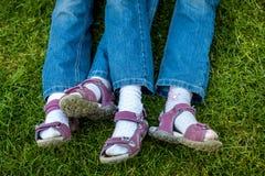 Piernas similares en las sandalias de muchachas gemelas Imagen de archivo libre de regalías