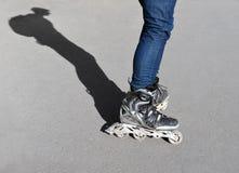 Piernas y adolescente de la sombra en pcteres de ruedas Imagen de archivo