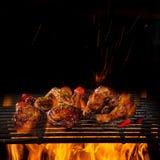 Piernas y alas de pollo en la parrilla con las llamas imagen de archivo libre de regalías