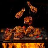 Piernas y alas de pollo en la parrilla con las llamas fotografía de archivo
