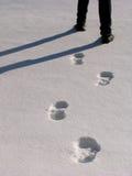 Piernas y huellas del hombre en la nieve Fotografía de archivo