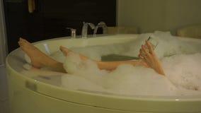 Piernas y mano femeninas atractivas con el vidrio de champán en baño caliente con la espuma que se relaja almacen de video