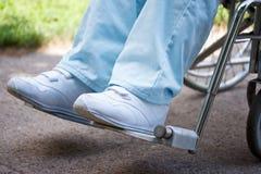 Piernas y pies de la mujer que se sientan en sillón de ruedas Imagenes de archivo
