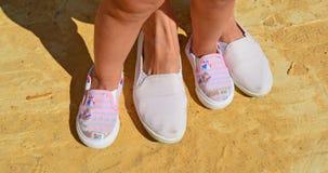 Piernas y pies del ` s de los niños en zapatillas de deporte del adulto de los zapatos fotos de archivo libres de regalías