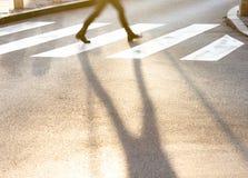 Piernas y sombra borrosas de un adolescente que cruza el stree de la ciudad Imagen de archivo libre de regalías