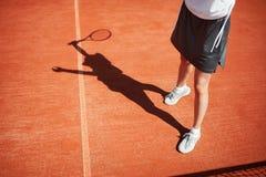 Piernas y sombra del jugador de tenis en campo de tenis Imágenes de archivo libres de regalías