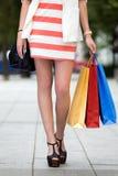 Piernas y talones de la mujer con los bolsos de compras Imágenes de archivo libres de regalías