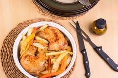 Piernas y verduras asadas de pollo en una cazuela Foto de archivo libre de regalías