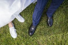 Piernas y zapatos de la novia y del novio en hierba verde Imagen de archivo
