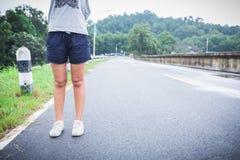 Piernas y zapatos de las mujeres de Yung que se colocan en la calle Imágenes de archivo libres de regalías