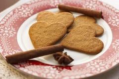 Piernikowi sercowaci ciastka z cynamonowymi kijami i anyż gwiazdami na czerwień talerzu fotografia stock