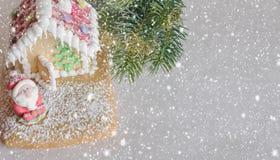 Piernikowy dom dekorował z kolorowymi cukierkami i Święty Mikołaj na śnieżnym tle Boże Narodzenie funda Dobro odbitkowa przestrze Zdjęcia Stock