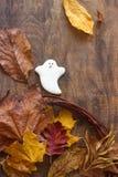 Piernikowy duch dla Halloween, dekorujący z jesień liśćmi na drewnianym tle, obrazy stock