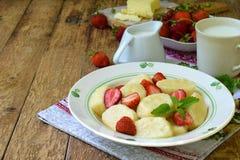 Pierogi сладостного завтрака ягоды сладостное ленивое, вареники с сметаной, масло и клубника на деревянной предпосылке Итальянско стоковое фото