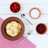 Pierogi doce com creme de leite, morangos e doce em um fundo vermelho-branco fotografia de stock