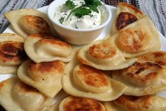 Pierogis with sour cream and fried onions Royalty Free Stock Photography