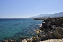 Pierre érodée de volcan à la plage et à l'eau bleue d'espace libre Photographie stock libre de droits