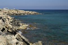 Pierre érodée de volcan à la plage et à l'eau bleue et au bleu d'espace libre Photo stock