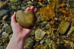 Pierre de coeur dans la paume avec la mer à l'arrière-plan Photos libres de droits