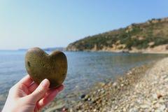 Pierre de coeur dans la paume avec la mer à l'arrière-plan Photo stock