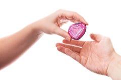 Pierre en forme de coeur comme cadeau chez la main de la femme Photos stock
