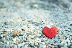 Pierre en forme de coeur sur le sable Photographie stock libre de droits