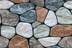 pierre multicolore avec le fond arrondi de mur de visages photo stock