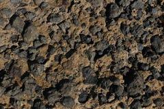 Pierre noire de lave incluse dans des écoulements de lave rouges consolidés images libres de droits
