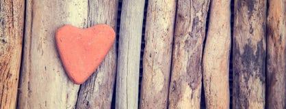 Pierre rouge sous forme de coeur sur le fond en bois Photo libre de droits
