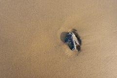 Pierre sous forme de flèche sur le sable Photo stock