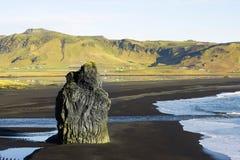 Pierre sur la plage noire de sable en Islande Photos stock
