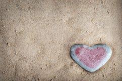Pierre teintée de coeur sur le sable Images stock