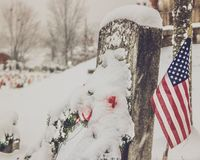 Pierre tombale dans la neige avec le drapeau photo stock