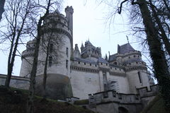 Pierrefonds Castle. In France on a cloudy evening with a view of the walls, façade, towers and some surrounding trees royalty free stock photography