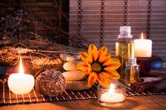 Pierres blanches, fleurs sèches, bougies, cannelle, huile, sur le tapis en bambou photos libres de droits