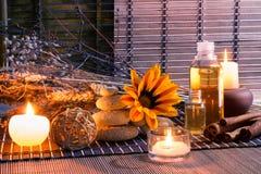 Pierres blanches, fleurs sèches, bougies, cannelle, huile, sur le tapis photo libre de droits