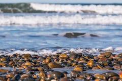 Pierres couvrant la plage d'état du sud de Carlsbad de vagues se brisantes image libre de droits
