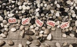 Pierres de caillou avec le texte allemand pour la chance, la force, l'amusement, l'amour et le PO Photo libre de droits
