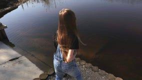 Pierres de lancement heureuses de petite fille dans le lac banque de vidéos